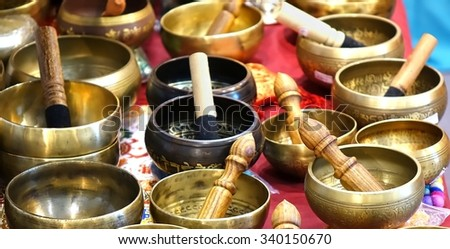 A collection of Tibetan singing bowls with mallets - stock photo