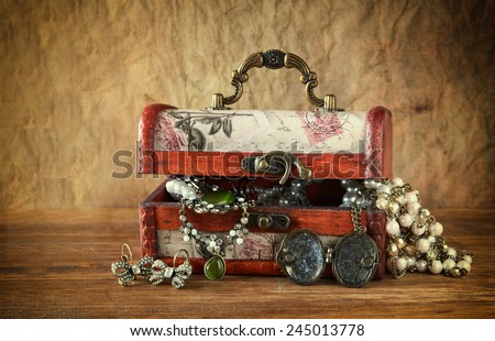 A collection of vintage jewelry in antique wooden jewelry box - stock photo