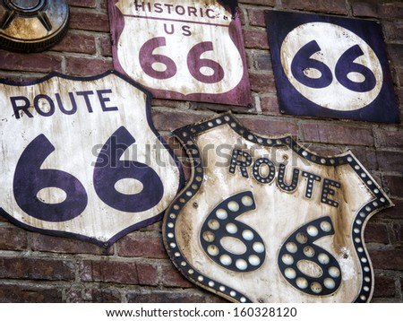 A Collection of vintage Route 66 signs displayed  on a old brick wall.  - stock photo