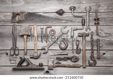 A collection of vintage tools displayed on a background of grey barnboard. - stock photo