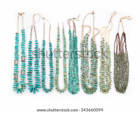 A Collection of Vintage Turquoise Native American Necklaces with Silver Beads and Tortoise Shell Heishe Beads which are strung on Catgut, on a white background. - stock photo
