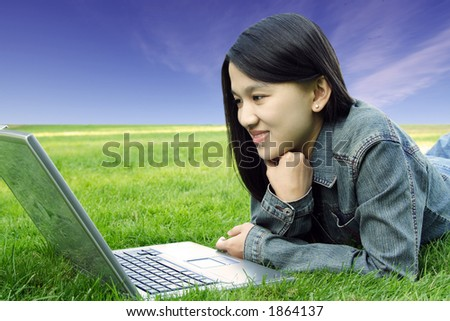 A college student with laptop in a park