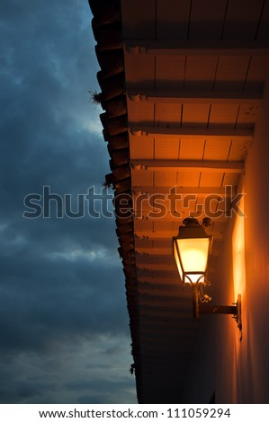 A colonial roof and light taken at dusk. - stock photo