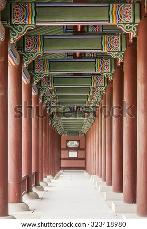 A colonnade at the Geunjeongmun Gate (or third gate) of the Gyeongbokgung Palace complex in Seoul, Korea shows the row of red columns topped by ornately painted wood beams. - stock photo
