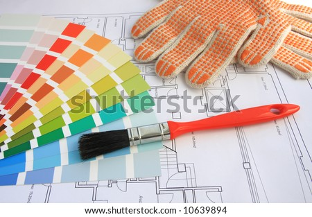 A color guide, a brush and gloves with a house plan on background - stock photo