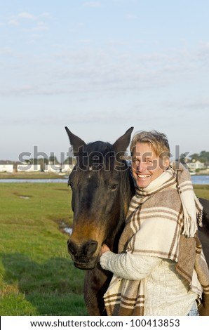 A color portrait photo of a handsome blonde man in his forties petting his brown horse.