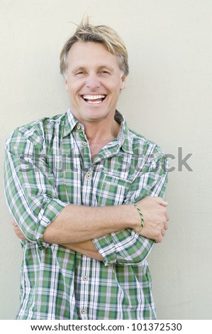 A color portrait photo of a happy laughing man in his forties wearing a green checked shirt against a plain wall backround.