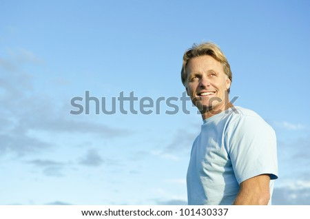 A color portrait photo of a happy smiling blond haired man in his forties wearing a blue t'shirt against a blue sky backround.