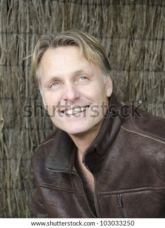 A color portrait photo of a happy smiling blond man in his forties wearing brown leather jacket. - stock photo