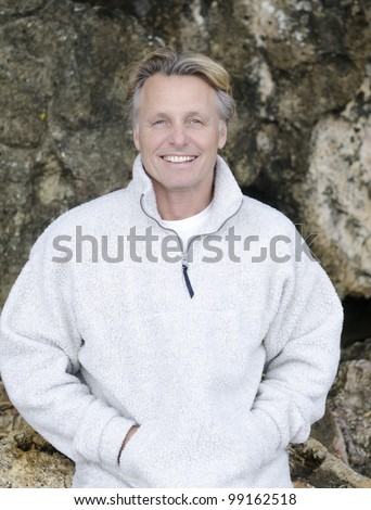 A color portrait photo of a happy smiling mature blonde man in his forties wearing a white fleece top and giving a warm friendly look towards the camera. - stock photo