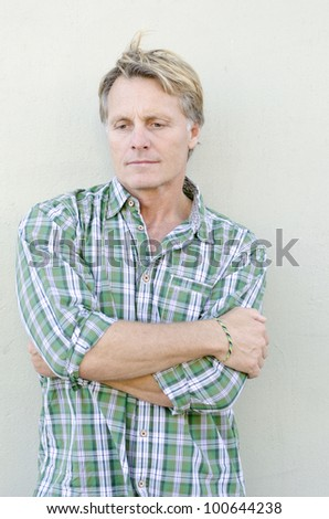 A color portrait photo of a pensive and sad looking mature man in his forties wearing a green checked shirt. - stock photo