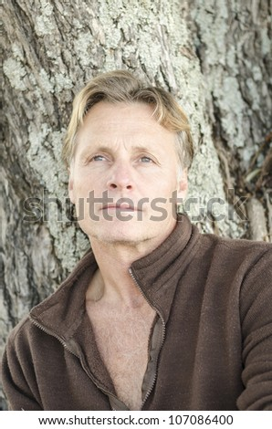 A color portrait photo of a pensive looking blond haired man in his forties wearing a brown pullover. - stock photo