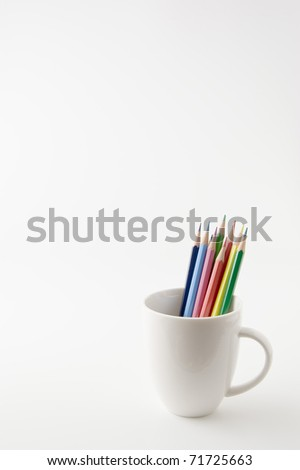 A colored pencil is put in a coffee cup. - stock photo