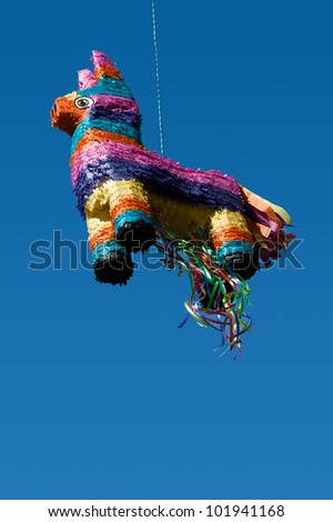 A colorful and festive pinata hangs from a rope ready to burst open. - stock photo