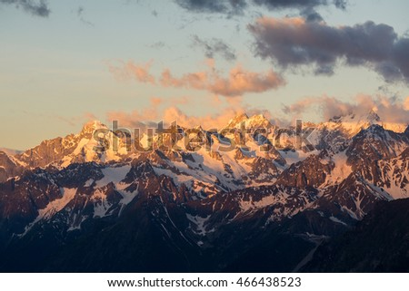 A colorful and partly clouded sunrise shot of Mont Dolent and Tour Noir, two prominent peaks above the Argentiere side of the Chamonix valley in the French alps.