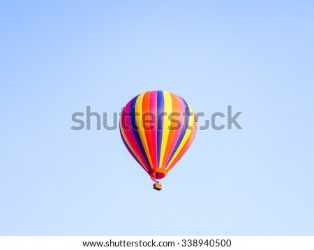 A colorful balloon flying in the middle of the bright blue sky