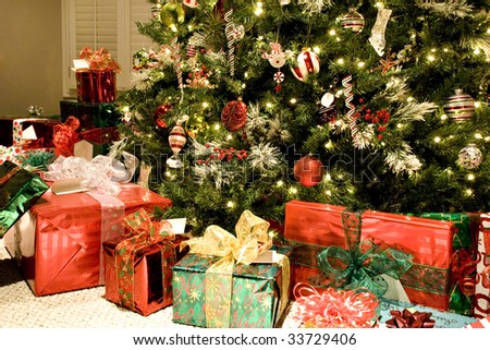 A colorful Christmas tree with lots of shiny wrapped gifts, beautiful ornaments and white sparkling lights, horizontal with copy space - stock photo