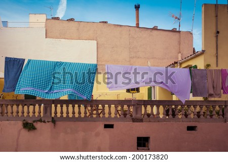 A colorful clothesline in front of an old house and a blue sky in Spain - stock photo