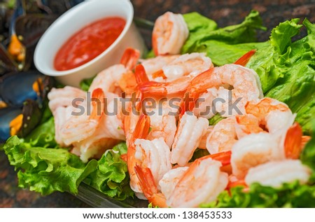 A colorful dish of cooked chilled shrimp with lettuce leaves