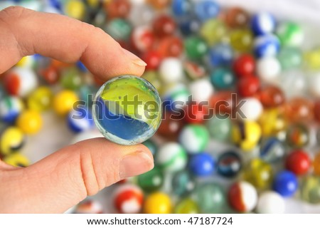 A colorful, earth-like marble being held in front of a background of many others - stock photo