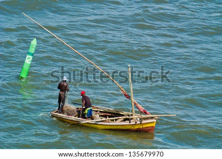 A colorful fishing dhow with 2 fishermen near Maputo - stock photo