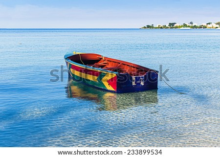 A colorful Jamaican boat floating along the shores of Bloody Bay, Negril. - stock photo