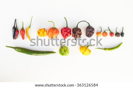 a colorful mix of the hottest chili peppers isolated on white. Thai chili, habanero, serrano, jalapeno, bhut jolokia, trinidad scorpion, carolina reaper, jamaican yellow, black chili