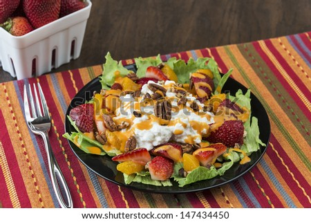 A colorful plate full of a refreshing fruit salad made with strawberries, mandarin oranges, cottage cheese, pecans and French dressing served over lettuce. One image in a series.