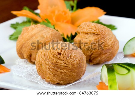 A colorful plate of Chinese Dim Sum puff pastry balls. - stock photo