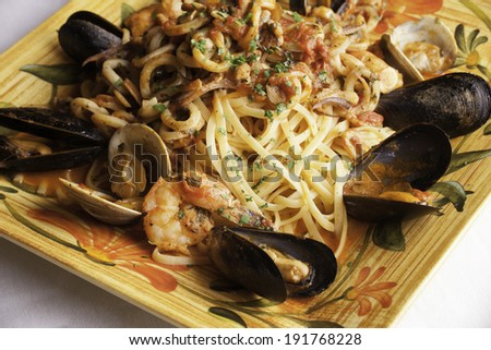 A colorful platter holds seafood fra diavolo over linguine.  Fresh littleneck clams, mussels, shrimp, and squid are piled over the linguini with fresh basil sprinkled on top. - stock photo