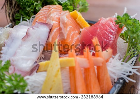 A colorful platter of sashimi sushi with tuna and crab sticks - Selective focus point - stock photo
