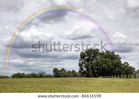 A colorful rainbow over a green pasture meadow against a dramatic stormy sky. This is a HDR image. - stock photo