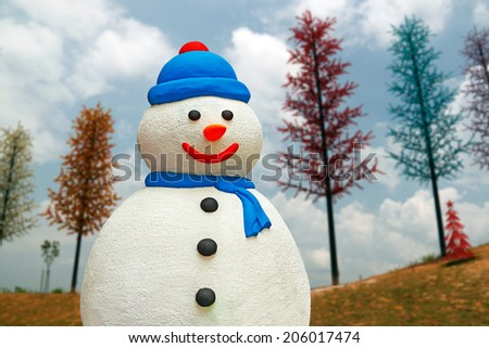 A colorful snowman against a magical landscape with colorful pine trees for Christmas theme. - stock photo