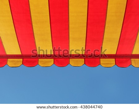 A colorful stripe canopy awning isolated against clear blue sky. - stock photo