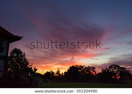 A colorful sunset over the Balinese homes, plantations and paddy fields, in Ubud, Bali Island. - stock photo