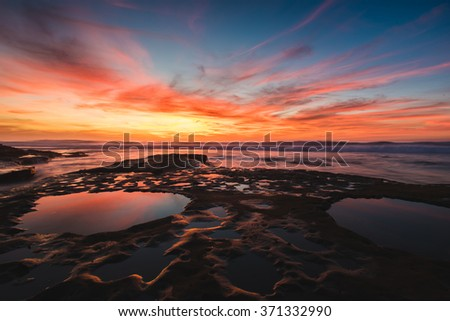 A colorful sunset reflects in the tide pools along the shore.  - stock photo