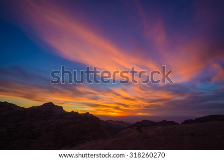 A colorful sunset seen from the mountains of ancient Petra in Jordan - stock photo