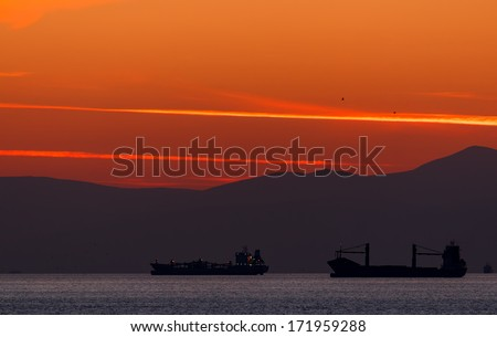 A colorful sunset with 2 anchored ships and birds flying at Piraeus, Greece - stock photo