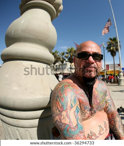 a colorful tattoo artist enjoys a summer day outside - stock photo