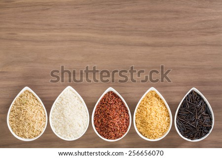 A colorful variety of rice in bowls, arranged as a border, over a wooden background - stock photo