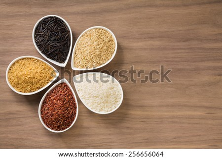 A colorful variety of rice in bowls over a wooden background - stock photo