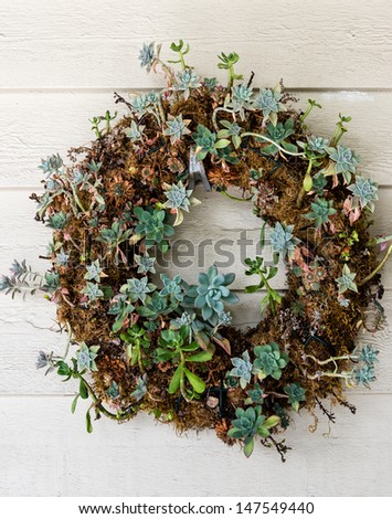 A colorful welcoming rustic wreath on wooden wall - stock photo