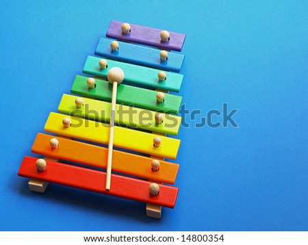 a colorful wooden xylophone over a blue background - stock photo