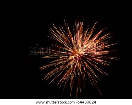 A colourful burst of fireworks in the night sky - stock photo