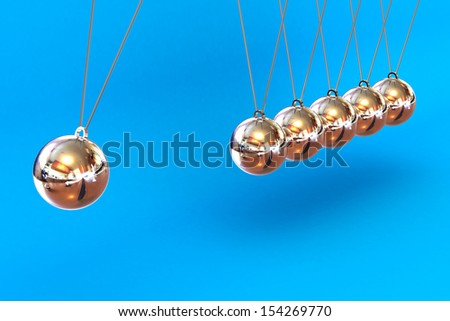 A Colourful 3d Rendered Newtons Cradle Illustration on a Blue Background - stock photo
