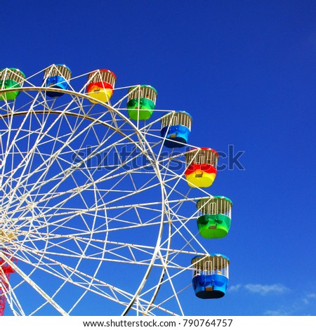 A colourful Ferris Wheel with clear blue sky as background