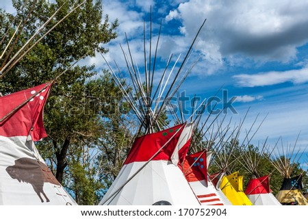 A colourful row of traditional Blackfoot plains Indian tepees in Alberta, North America, at the Calgary Stampede. - stock photo