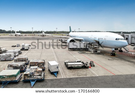 A commercial aircraft being serviced on the tarmac of an international airport. - stock photo