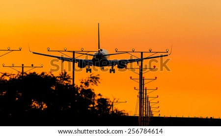 A commercial jet preparing for landing during sunset with landing lights lit.