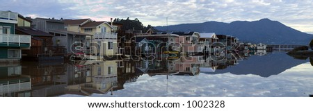 A community on the water in Sausalito, CA. Suburbia built on rafts, on a calm clear morning in late January. The bay is calm as glass, perfectly reflecting houses and Mt. Tamalpais.